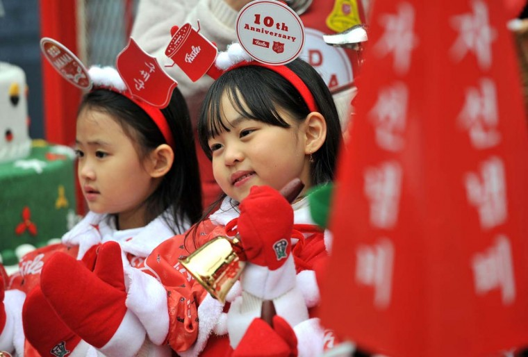 South Korean children wearing Santa Claus outfits hold bells during a ceremony to prepare charity pots for a year-end fund-raising campaign at Seoul Plaza in Seoul on November 27. The Salvation Army will launch its year-end charity campaign for poor people from December 2. AFP/Getty Images