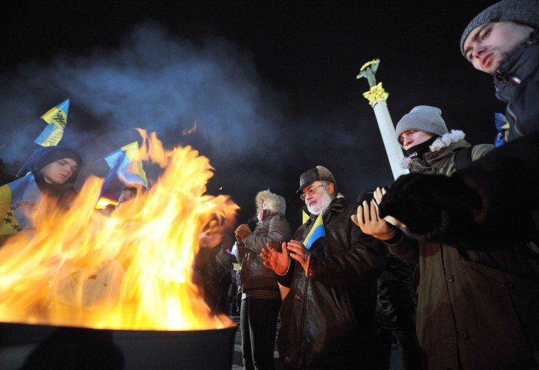 People warm themselves around a bonfire during a rally of the pro-European movement in central Kiev, on November 27, 2013, on the fourth day of protests over the government's decision to scrap a key pact with the EU. (GENYA SAVILOV/AFP/Getty Images)