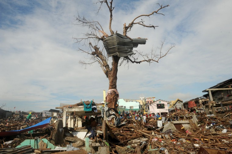 "This photo taken on November 27, 2013 shows typhoon survivors (in background) participating in a ""cash for work"" program, cleaning debris from destroyed houses in Tacloban, Leyte province. (NOEL CELIS/AFP/Getty Images)"