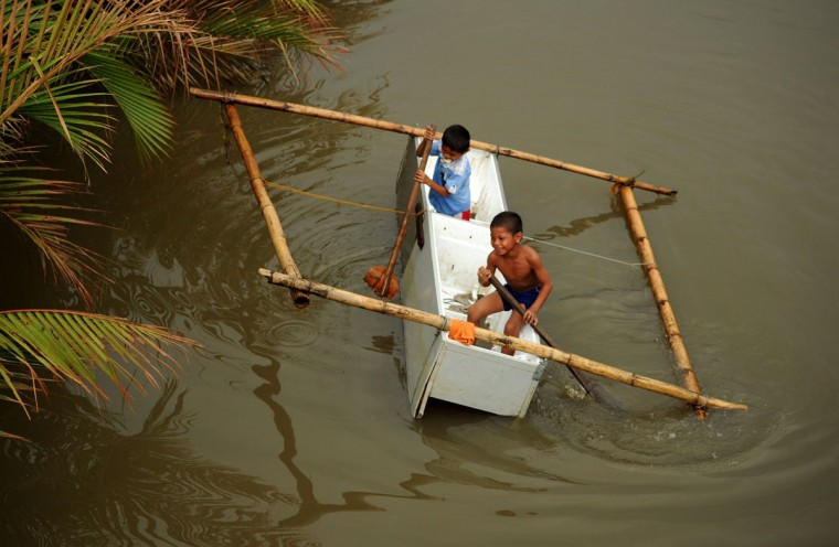 Children use a makeshift boat made from a damaged refrigerator in a river in Basay, Samar province on November 28, 2013. (NOEL CELIS/AFP/Getty Images)