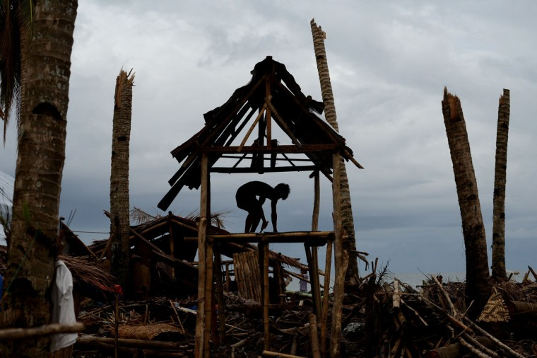 A man rebuilds his damaged house in Basay, Samar province on November 28, 2013. (NOEL CELIS/AFP/Getty Images)