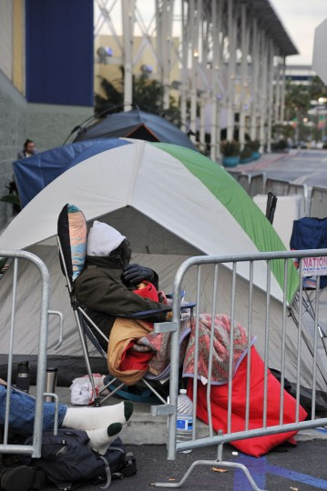 A man tries to stay warm while waiting in line outside the Best Buy store in Burbank, California for the store to open on Thanksgiving Day, November 28, 2013. More than a dozen US retailers will open their doors to shoppers one day ahead of the famed-Black Friday shopping day. (Robyn Beck/AFP/Getty Images)