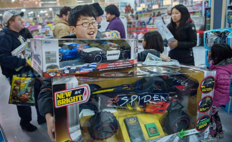 A young shopper carries large toys towards the check-out register on Black Friday, seen here on Thursday November 28, 2013, at the Toys-R-Us store in Fairfax, Virginia. More than a dozen US retailers opened their doors to shoppers one day ahead of the famed-Black Friday shopping day. (Paul J. Richards/AFP/Getty Images)