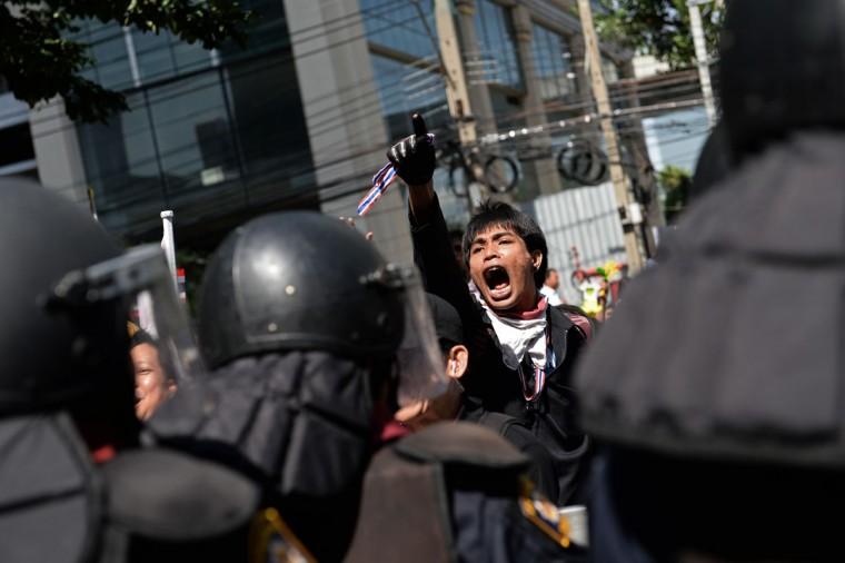 A Thai opposition protester shouts slogans as protesters face off with police deployed to guard the ruling Puea Thai party headquarters in Bangkok on November 29, 2013. Defiant Thai opposition protesters stormed the army headquarters and besieged Prime Minister Yingluck Shinawatra's party offices on November 29, intensifying their fight to bring down her government. (Christophe Archambault//AFP/Getty Images)