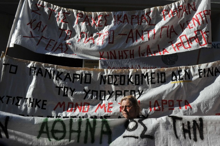 A protester stands between banners against the closure of the only health centre on the island of Ikaria, as public sector's doctors and medical staff protests outside the Ministry of Health on November 29, 2013 in Athens. Medical staff extended their strike started on November 25th until December 9th, against government's plans to suspend and reallocate staff . (Louisa Gouliamaki/AFP/Getty Images)