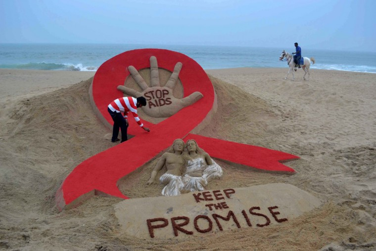 Indian sandartist Sudersan Pattnaik gives the final touches to a sand sculpture on the eve of World AIDS Day, as a horseman rides by on Golden Sea Beach in Puri, some 65 kms east of Bhubaneswar on November 29, 2013. World AIDS Day is celebrated on December 1, every year to raise awareness about HIV/AIDS and to demonstrate international solidarity in the face of the pandemic. (Asit Kumarstrdel/AFP/Getty Images)