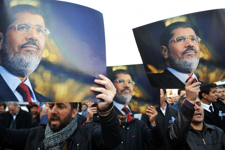 Protestors hold pictures of ousted Egyptian President Mohamed Morsi and chant slogans on November 29, 2013 during a pro-Morsi rally in Istanbul. A group of Islamist protesters gathered in front of the Fatih mosque after Friday prayer in support of detained Muslim Brotherhood leaders in Egypt. Clashes erupted in Cairo and other Egyptian cities Friday as police dispersed protests staged by Islamists defying a new law banning unauthorised demonstrations, security officials said. (Ozan Kose/AFP/Getty Images)