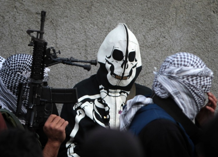 An armed Palestinian, member of the Al-Aqsa Martyrs' Brigade, a group linked to the Fatah movement, is dressed in a skeleton outfit as he takes part in the funeral of Mahmud Waji Awad, a Palestinian man who died the previous day of his injuries after he was shot in a 2012 clash with Israeli troops, in the West Bank's Qalandiya camp on November 29, 2013. (Abbas Momani/AFP/Getty Images)