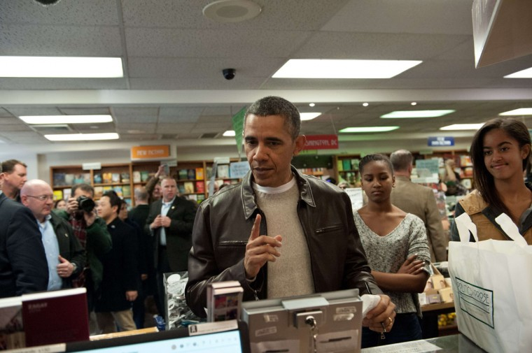 US President Barack Obama speaks to a cashier as he pays for books with daughter Malia (R) and Sasha (C) at the Politics and Prose bookstore in Washington on November 30, 2013 as part of Small Business Saturday. (Nicholas KammAFP/Getty Images)