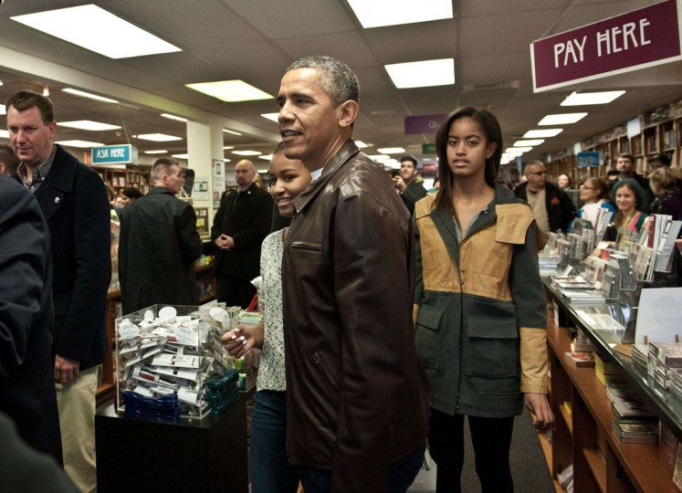 US President Barack Obama and daughter Malia (R) and Sasha (L) leave the Politics and Prose bookstore in Washington on November 30, 2013 after buying books as part of Small Business Saturday. (Nicholas Kamm/AFP/Getty Images)