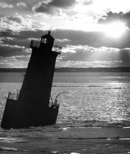 1/28/1977 - The lighthouse at Sharp Point in the Chesapeake Bay, 3 miles southwest of Black Walnut Point near Tilghman Island, is leaning at a 20-degree angle as a result of ice pressure against the navigational facility's cylindrical concrete base. (Weyman Swagger/Baltimore Sun)