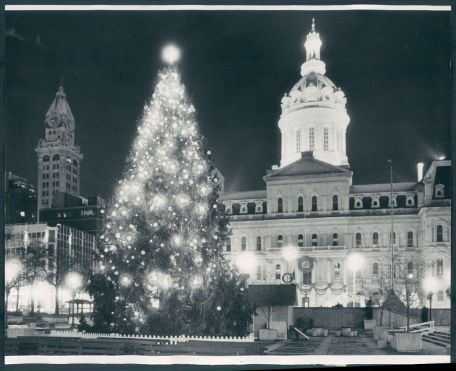 The great clock on the now-demolished Tower Building, at left, reads 8:25 p.m. on Christmas Eve 1982. City streets are deserted and there is no one about -- including Santa Claus, who has other obligations -- to take in the illuminated City Hall dome and the Christmas tree that towers over City Hall Plaza. Photo by George Cook