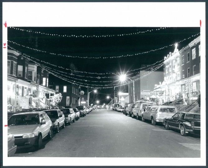 The annual outdoor kilowatt explosion of Hampden's 34th Street, depicted here in 1991, has for years been a destination for visitors from all over the nation and world. They chug through the neighborhood in cars and buses or stroll its sidewalks to observe. Publications including The New York Times have called attention to this spectacle of light and Christmas kitsch. Photo by Gene Sweeney Jr.