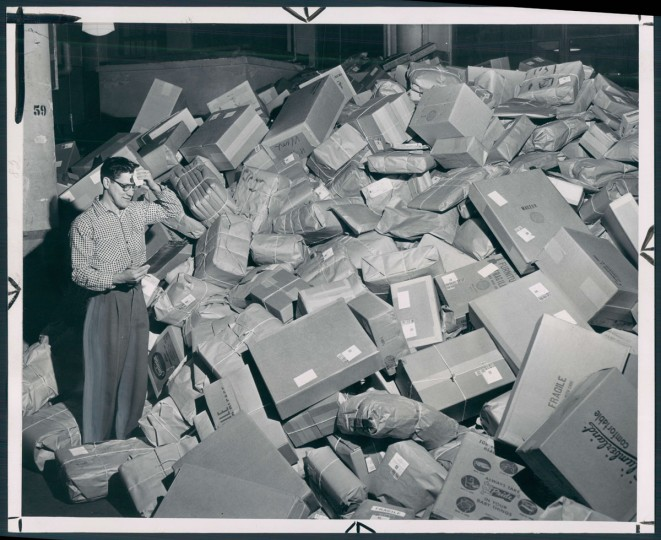 No wonder postal worker Edward Sadeck is wiping his brow as he stares at the mountain of packages that must reach their destinations by Christmas Day. He had better get busy. It is Dec. 15, 1955, and he has less than 10 days to go. Photo by William L. Klender