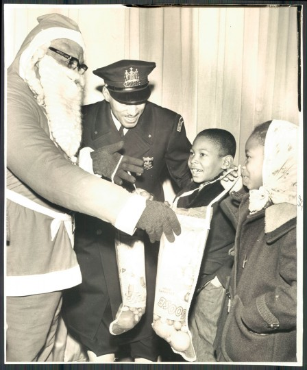 "Santa (aka Creston ""Doc"" Woingust) is joined by patrolman Alfred C. Smith as they give stockings to a brother and sister, Everett, 8, and Wanda Loggins, 7, in a 1963 Western District Christmas party at the old Royal Theater on Pennsylvania Avenue. Photo by William L. LaForce Jr."