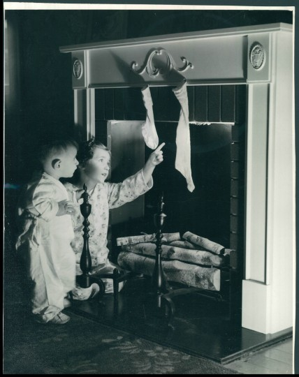 A brother and sister double-check to make sure that no Christmas Eve fire is burning and that their father left the flue open so Santa can safely travel from roof to parlor in this 1939 scene. Sun file photo