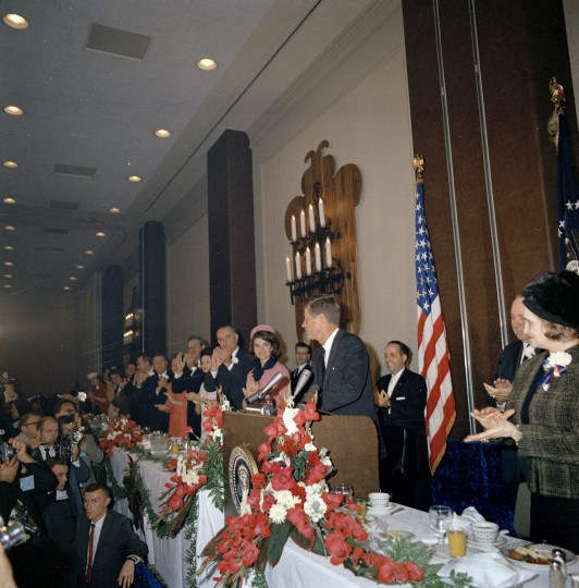 President Kennedy stands behind the lectern at the Fort Worth Chamber of Commerce breakfast at the Hotel Texas in Fort Worth, Texas. Nellie Connally, Texas Gov. John Connally, Lady Bird Johnson, Vice President Lyndon B. Johnson and first lady Jacqueline Kennedy applaud to the president's left. (Cecil Stoughton/John F. Kennedy Presidential Library and Museum/MCT)