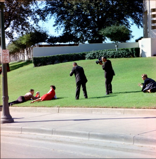 At 12:30 p.m. (CDT), three shots ring out as the president's motorcade passes through Dealey Plaza in Dallas. Frightened onlookers cover their children on the grass in the Plaza, as cameramen record their actions. President Kennedy is struck by two shots, and Gov. Connally wounded. (Cecil Stoughton/John F. Kennedy Presidential Library and Museum//MCT)