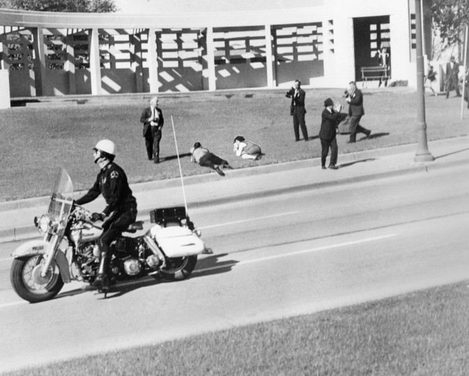 As spectators lie on the ground in Dealey Plaza and cameramen roll their cameras, a motorcycle police officer drives by immediately after the shooting of the president. (Tom Dillard/Dallas Morning News/MCT)
