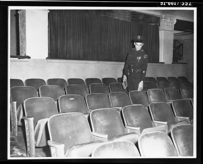 With a police manhunt underway, Oswald takes refuge in the Texas Theater in Dallas. Shortly before 2:00 p.m. (CDT), police arrest Oswald in the back of the movie house. An unknown police officer inside the theater points to the seat where Oswald sat. (Dallas Police Department/Dallas Municipal Archives/MCT)