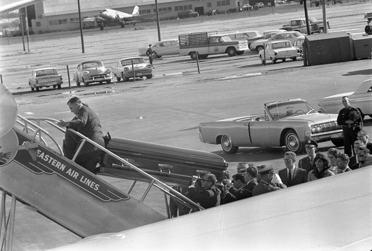"""President Kennedy's casket is loaded on to Air Force One at Love Field in Dallas, Texas, for flight to Washington, D.C. Onlookers include Lawrence """"Larry"""" O'Brien, Jacqueline Kennedy and Dave Powers. (Cecil Stoughton/John F. Kennedy Presidential Library and Museum/MCT)"""