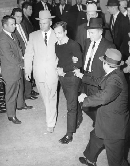 Local businessman Jack Ruby, foreground, approaches and fires a gun at Lee Harvey Oswald, center, in handcuffs, as he is escorted to the Dallas city jail via the underground garage of the Dallas police headquarters, Texas, on Nov. 24. Oswald is escorted by detectives Jim Leavelle, left, who is handcuffed to Oswald, and L.C. Graves, right. Oswald later dies at a hospital. (Jack Beers/Dallas Morning News/MCT)