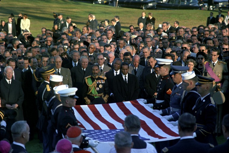 Pallbearers hold the U.S. flag during the burial service for President Kennedy at Arlington National Cemetery in Arlington, Va., on Nov. 25. Dignitaries include French President Charles de Gaulle, President of West Germany Ludwig Erhard, Emperor Haile Selassie of Ethiopia, Queen Frederica of Greece and King Baudoin of Belgium. (Cecil Stoughton/John F. Kennedy Presidential Library and Museum/MCT)