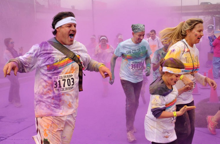 Runners pass through a cloud of purple outside M&T Stadium in the morning Color Run. (Amy Davis / The Baltimore Sun)