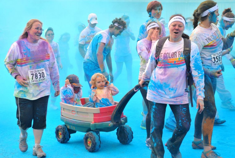 Kelly Zajicek of Bel Air pulls a wagon with her son Declan, 3, in front, and a friend, Dominic Navarrete, 5, in back of wagon, who is trying to avoid getting sprayed during the morning Color Run. (Amy Davis / The Baltimore Sun)