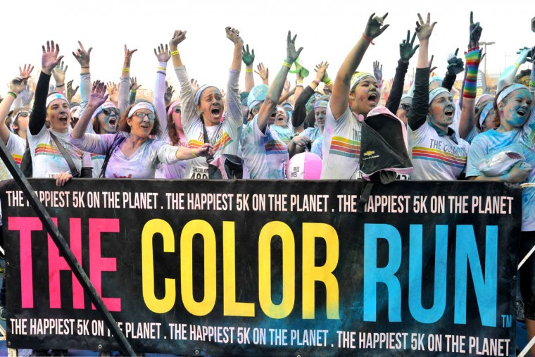 Runners cheer in response to entertainers on the stage at the party after the morning Color Run. (Amy Davis / The Baltimore Sun)