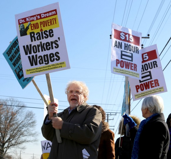 Charlie Cooper, 66, holds a sign in protest outside the Towson Walmart on Joppa Road this Black Friday. Protestors gathered on one of the biggest shopping days of the year to demand higher wages and equality from the world's biggest chain. (Kaitlin Newman/Baltimore Sun)
