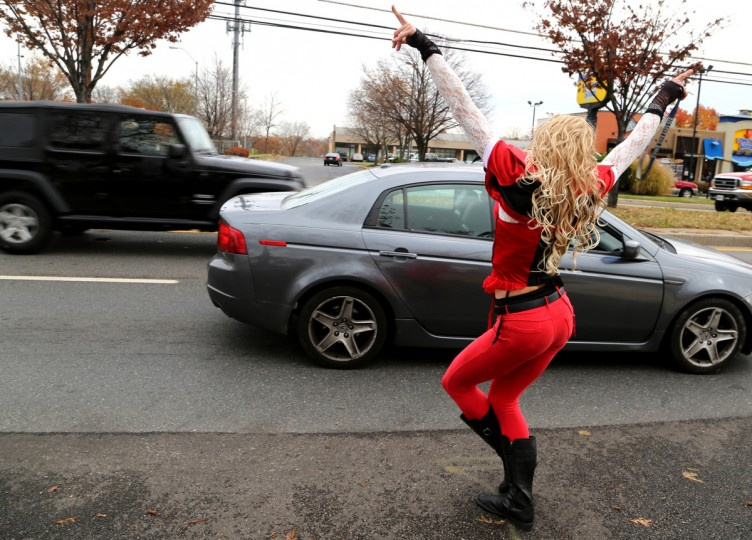 Dale Crites, dressed as BritneyGirl Dale walks along Ritchie Highway, posing in front of stopped cars. Crites usually walks away with smiles and waves. (Kaitlin Newman/Baltimore Sun)