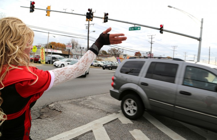 Dale Crites dressed as BritneyGirl Dale waves to drivers and other pedestrians. Despite being banned for life from the nearby shopping center off of 16th Street, Crites still walks the perimeter. (Kaitlin Newman/Baltimore Sun)