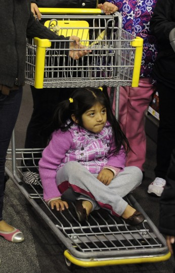 Five year old Brianna Lopez of Baltimore rides on the bottom of a cart at Best Buys. She and her family waited several hours outside the store for the chance at Thanksgiving bargains on laptop computers. (Barbara Haddock Taylor/Baltimore Sun)
