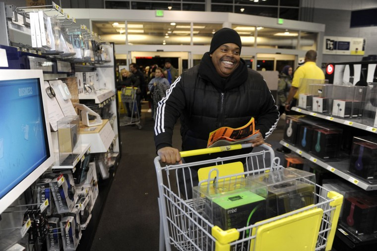 James Williams of Baltimore was the first shopper in line this morning at Best Buys. Here, he smiles broadly after grabbing some items on his way into the store. (Barbara Haddock Taylor/Baltimore Sun)