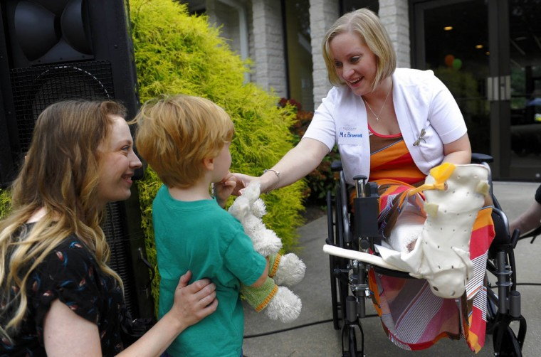 Erika Brannock, who was injured in the Boston Marathon bombing, was the guest of honor Aug. 22 at the ribbon-cutting ceremony at the new Davenport Preschool. Many of her former students will be attending the new school. Here, Brannock greets Henry Smith, 3, and his mother, Jessica Smith, before the ceremony. The school also dedicated a garden to Brannock. (Barbara Haddock Taylor/Baltimore Sun)