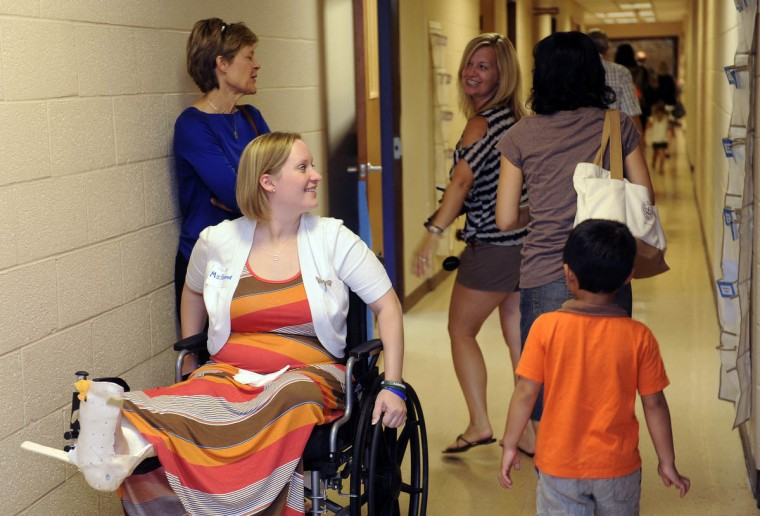 Erika Brannock, left, was the guest of honor at the ribbon cutting ceremony at the new Davenport Preschool. Here, she tours the halls of the new school as she's greeted by students, parents and staff. Many of her former students will be attending the new school. The school also dedicated a garden to Ms. Brannock. (Barbara Haddock Taylor/Baltimore Sun)