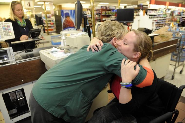 Erika Brannock hugs cashier Pat Groft at Graul's grocery store. (Barbara Haddock Taylor/Baltimore Sun)