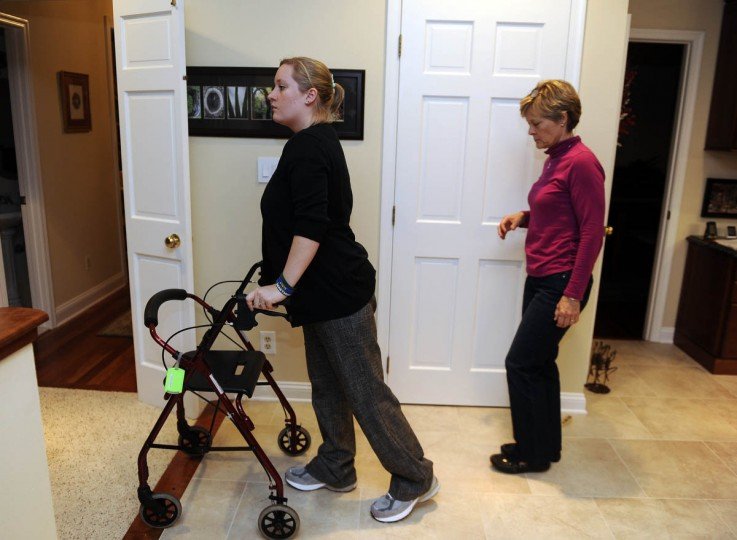 Erika Brannock uses a walker which once belonged to her grandmother as she walks through her family's kitchen. Her mother, Carol Downing, is on right. (Barbara Haddock Taylor/Baltimore Sun)