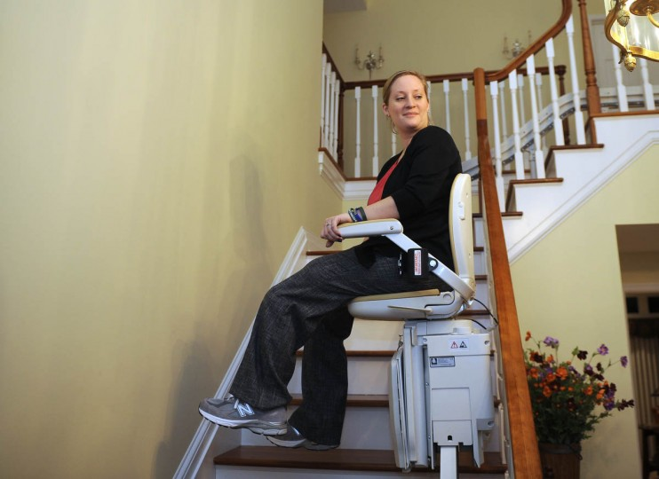 """Erika Brannock uses a stairlift she calls her """"personal rollercoaster"""" to get to her second floor bedroom in her family's home. (Barbara Haddock Taylor/Baltimore Sun)"""