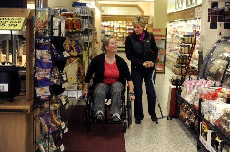 Erika Brannock goes through the store with her mother, Carol Downing, who is carrying Erika's cane. (Barbara Haddock Taylor/staff)