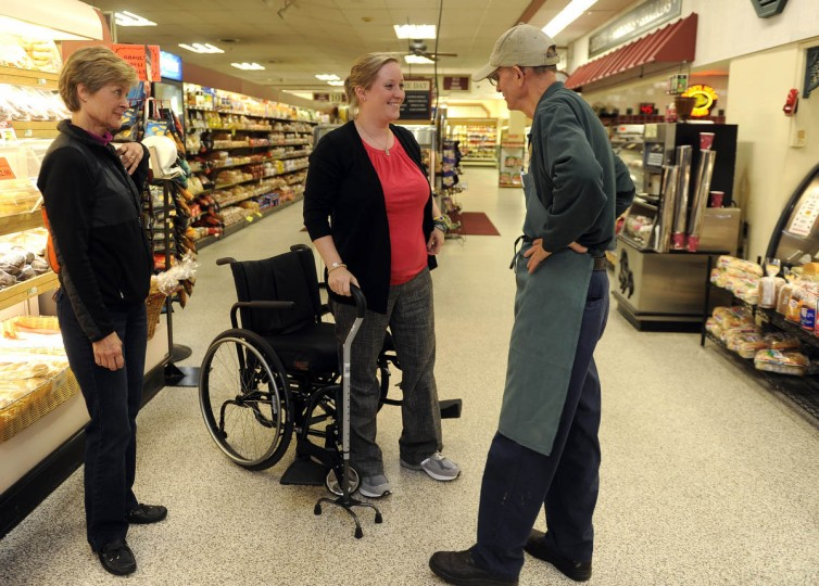 Erika Brannock, center, who lost her left leg in the Boston Marathon bombing, visits Graul's grocery store, where she worked for 6 years. Here, she talks with deli manager Ron Hohman, right, as her mother Carol Downing stands on left. (Barbara Haddock Taylor/Baltimore Sun)