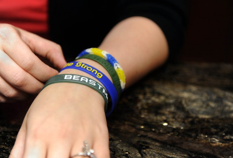 """On her wrist Erika Brannock wears rubber bracelets: one from a surgeon says, """"Beastmode,"""" and the two others say, """"Strong Brannock"""" and """"Be Strong,"""" for the nonprofits set up for her recovery funds. (Barbara Haddock Taylor/Baltimore Sun)"""