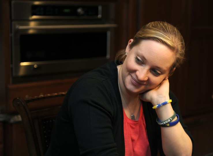 "Erika Brannock, who lost her left leg in the Boston Marathon bombing, sits in her family's kitchen. Brannock is wearing rubber bracelets: one from a surgeon says, ""Beastmode"" and two others say, ""Strong Brannock"" and ""Be Strong,"" for the nonprofits set up for her recovery funds. (Barbara Haddock Taylor/Baltimore Sun)"