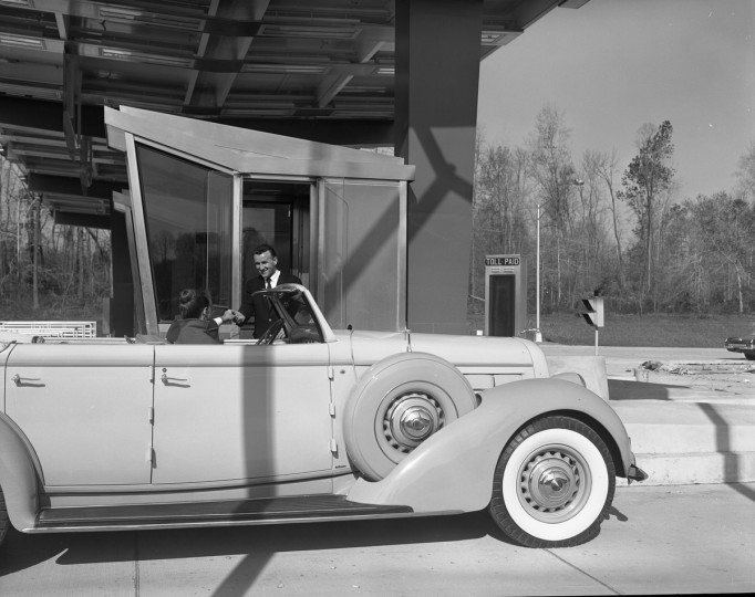 Toll Collector Joseph Rybicki, Sr., greats the Ceremonial first car through the Delaware Turnpike toll plaza on November 14, 1963. (Division of Motor Vehicles)