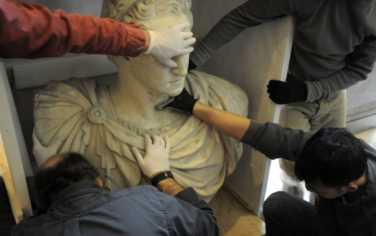 Hands secure the bust as it is taken out of the crate at the Walters Art Museum. (Lloyd Fox/Baltimore Sun)