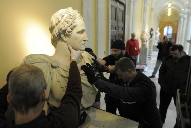 The bust of Washington is lifted onto a pedestal at the Walters Art Museum after being moved from the museum at the base of the Washington Monument. (Lloyd Fox/Baltimore Sun)