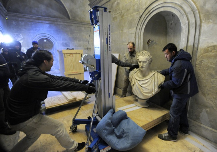L-R Chai Longnecker, Joe Hoffman and Anthony Tran of Bonsai Fine Arts, Inc help move The 1,000-pound bust of President George Washington. (Lloyd Fox/Baltimore Sun)