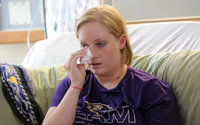Erika Brannock wipes away tears as she talks about the Boston Marathon bombings and life since losing her left leg below the knee and multiple surgeries to save her right leg. On left is a scarf given to her by Amanda North, the woman who helped save her life. Brannock is recovering from a recent surgery at the University of Maryland Medical Center. (Kim Hairston/Baltimore Sun)