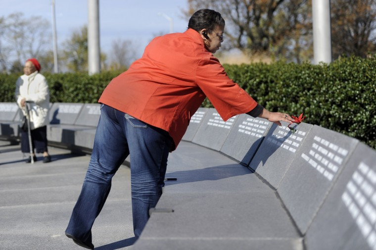 Gloria Baily of Baltimore places a flower on the name of her brother, James L. Harris, who was killed in 1968. She and her mother attended a Veterans Day remembrance at the Vietnam Veterans of Maryland Memorial this morning. (Barbara Haddock Taylor/Baltimore Sun)
